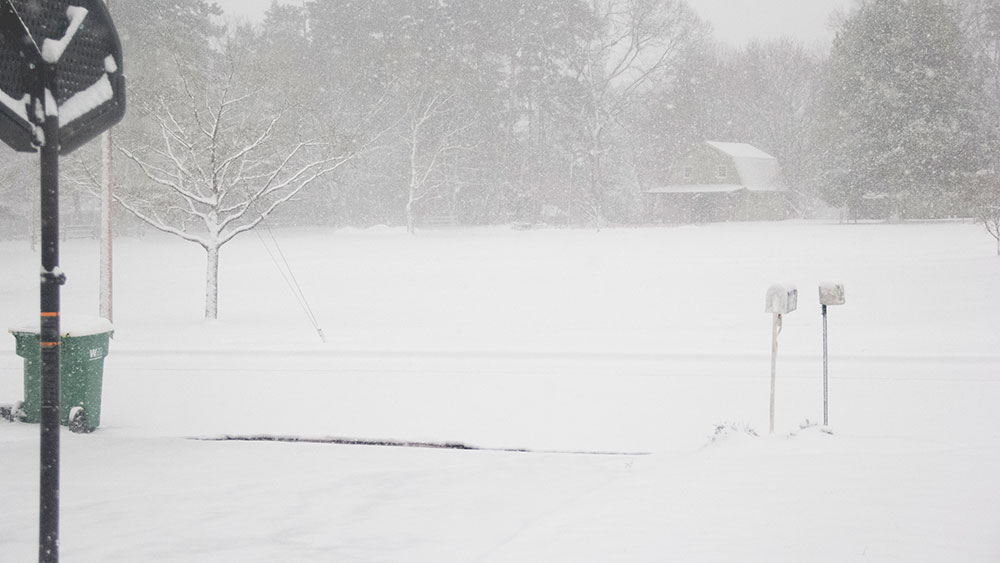 snow in salisbury, road is covered, a barn is in the distance