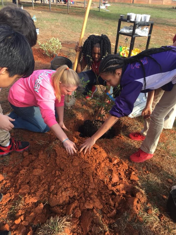 students and teacher gardening